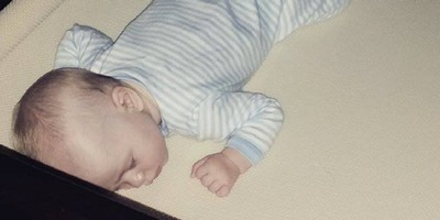 SafeSleep-Crib-Mattress-testimonial by Kelsi Peterson with her baby boy on his belly on his crib mattress